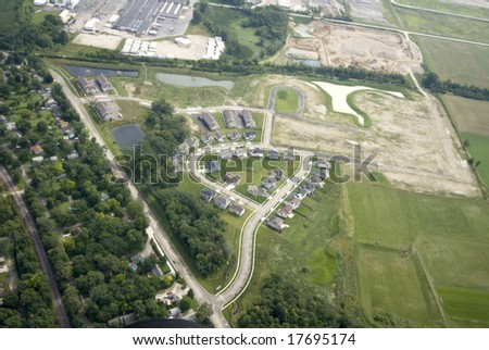 Overhead view of a green field of trees and homes