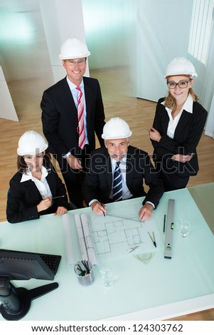 Overhead view of a group of architects or structural engineers discussing a blueprint laid out on the table in front of them