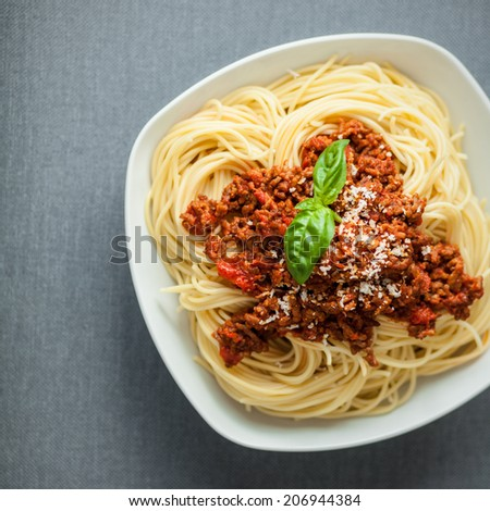 Overhead view of a large bowl of traditional Italian spaghetti pasta with a rich tomato and ground beef Bolognese topping garnished with fresh basil and parmesan cheese