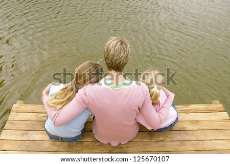 Overhead view of a mother and her two young daughters sitting close together on the end of a jetty overlooking a lake
