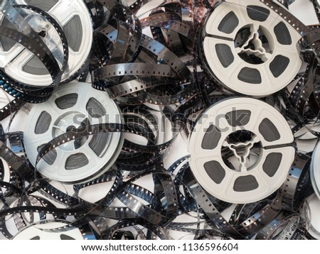 Overhead view of a pile of discarded, more than 50-year old and faded 8 millimeter movie film with equally old and dirty, dusty plastic film reels, which were considered high technology at the time