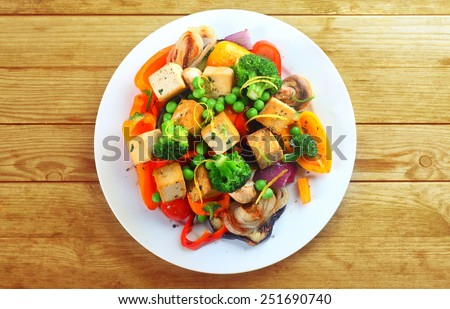 Overhead view of a plate of healthy grilled roast vegetables with tofu, or soybean curd, on a wooden table #251690740