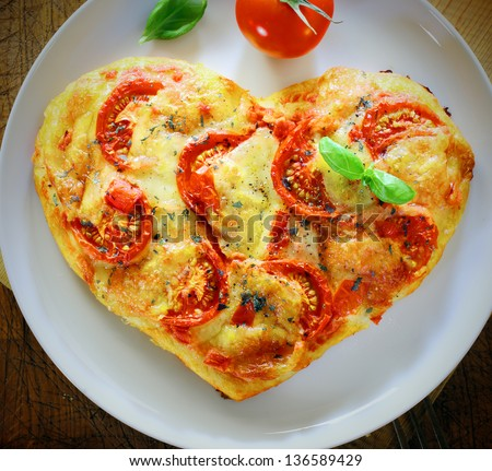Overhead view of a romantic heart shaped Italian pizza topped with a vegetarian topping of golden melted cheese and tomato on a plain white plate. More pizza at my port.