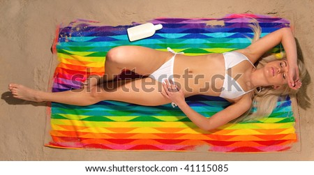 Overhead view of a slim blonde woman in a white bikini lying on a colorful beach towel sunbathing.