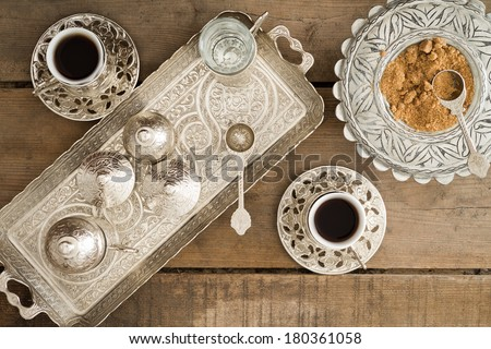 Overhead view of a tray set with cezve for heating the pulverised or ground coffee beans and two cups of freshly brewed traditional Turkish coffee served with brown sugar