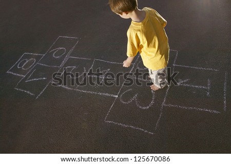 Overhead view of a young boy in a yellow shirt playing hopscotch marked out on an apshalt surface