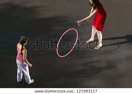 Overhead view of a young mother and her daughter throwing a hula hoop on a tarmac surface