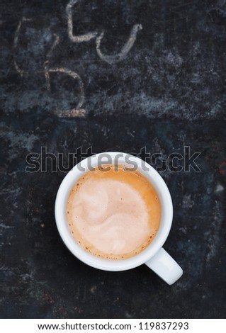 Overhead view of an aromatic frothy cup of freshly brewed cappuccino standing on a grungy old blackboard slate with chalk scribblings and copyspace