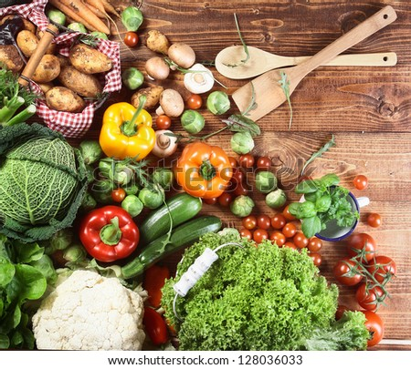 Overhead view of an array of different fresh country herbs and vegetables on a wooden kitchen surface ready to be used as ingredients in vegetarian cuisine