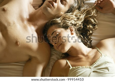 Overhead view of an attractive young couple laying down in bed, sleeping in a warm light.