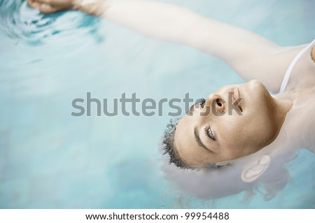 Overhead view of an attractive young woman floating on blue water.