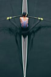 Overhead view of an oarsman in a single scull boat on calm water mid stroke, motion blur.