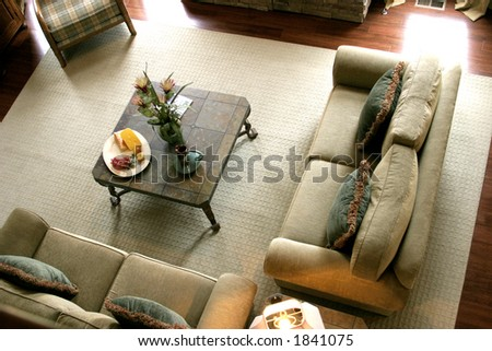 Overhead view of an upscale living room. two couches and coffee table on large rug