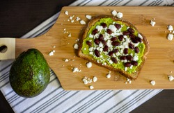 Overhead view of avocado toast with black beans and feta cheese on a wood cutting board