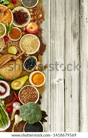 Overhead view of bed of herbs and bowls of beans and rice halfway covering rustic wooden plank background #1418679569