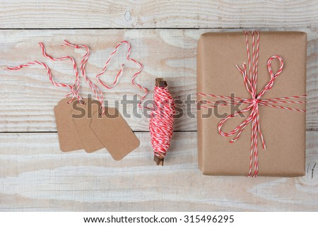 Overhead view of blank gift tags a spool of string and a plain brown paper wrapped present on a rustic whitewashed wood table.