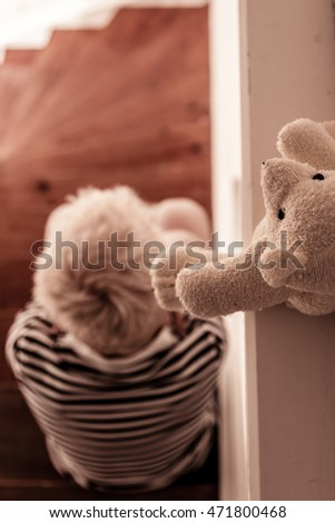 Overhead view of blond child seated on stairs and wearing stripped shirt as his teddy bear sits high above him #471800468
