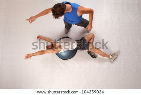 Overhead view of bold man man training with personal trainer on hemisphere
