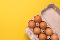 Overhead view of brown chicken eggs in an open egg carton isolated on yellow. Fresh chicken eggs background.  Top view with copy space. Natural healthy food and organic farming concept. Eggs in box