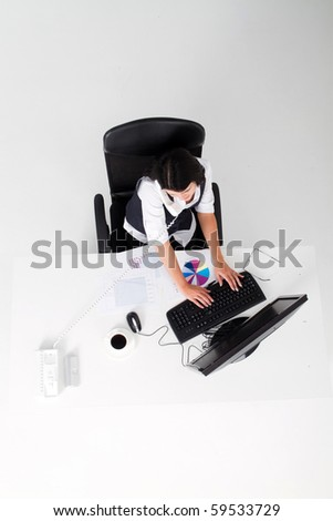 overhead view of businesswoman answering phone and working on computer
