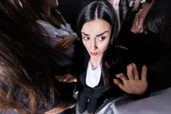 overhead view of businesswoman suffering from claustrophobia in crowded elevator