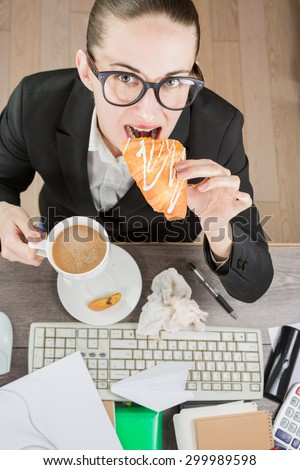 Overhead View Of Businesswoman Working and eating At Computer In Office. Coffee break with croissant