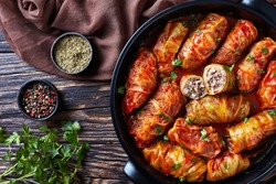overhead view of cabbage rolls stuffed with ground beef and rice and baked to perfection with a tangy tomato sauce in dutch oven, flatlay, close-up