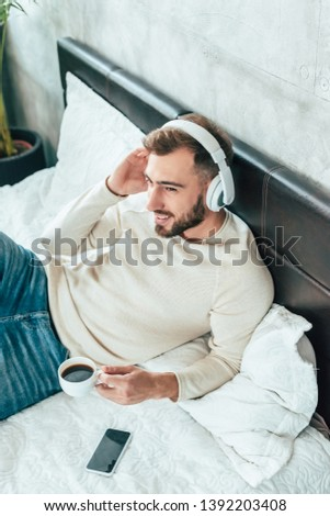 overhead view of cheerful man listening music in headphones while holding cup of coffee in bed  #1392203408