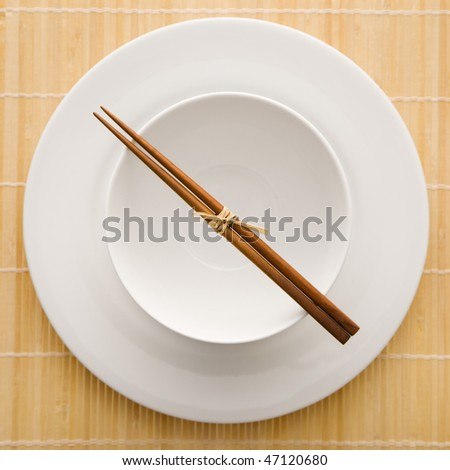 Overhead view of chopsticks lying across an empty bowl that is sitting on a plate on a bamboo mat. The dishes are white. Square shot.