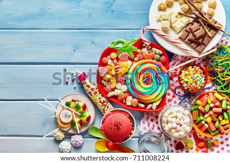 Overhead view of colorful array of different childs sweets and treats in bowls on light blue wood background #711008224