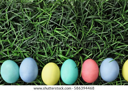 Overhead view of colorful Easter eggs lined up in a row over a background of grass. Flat lay style.