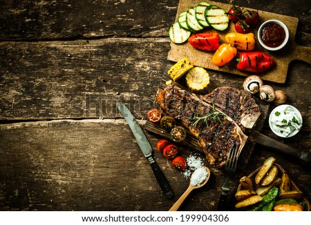 Overhead view of colorful roast vegetables, savory sauces and salt served with grilled t-bone steak on a rustic wooden counter in a country steakhouse #199904306