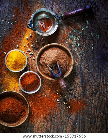 Overhead View Of Colourful Dried Ground Spices In Bowls Spilling Onto An Old Aged Scored Wooden Surface In A Country Kitchen With A Vintage Sieve Or Strainer