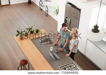 Overhead View Of Couple Looking At Laptop In Modern Kitchen