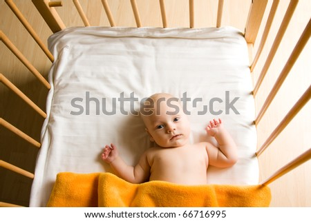Overhead view of cute baby boy lying under blankets in wooden crib or cot.