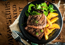 Overhead view of delicious,grilled beef steak with roasted pumpkin and fresh green herb salad on an old wooden packing case with printed text