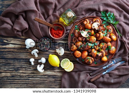 overhead view of delicious lightly fried champignons, Champinones Al Ajillo on an earthenware plate on an old rustic wooden table with brown cloth and ingredients, traditional spanish cuisine, flatlay #1341939098