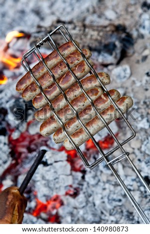 Overhead view of delicious sausages grilling over the glowing coals of a camp fire