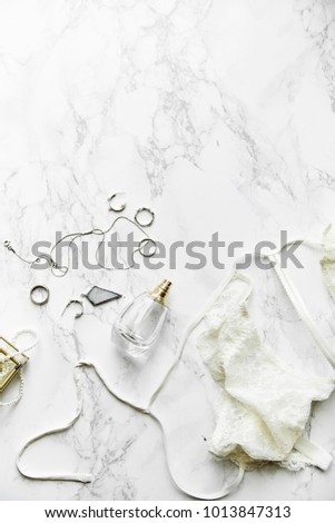 Overhead view of female lace lingerie, perfume and jewelry items on white marble background. Top view, text space. Monochromatic concept #1013847313