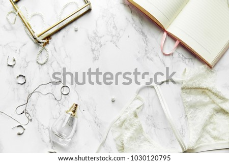 Overhead view of female lace lingerie, perfume and jewelry items on white marble background. Top view, text space. Monochromatic concept #1030120795