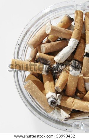 overhead view of glass ashtray full of cigarette stubs