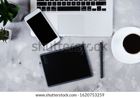 Overhead view of graphic tablet, graphic pen, smartphone, laptop and a cup of black coffee.