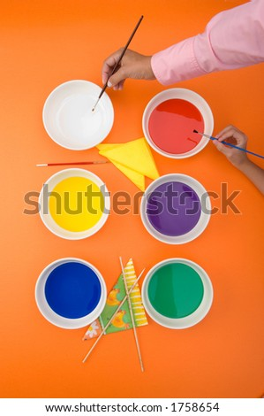 overhead view of hands with paint and brushes - stock photo