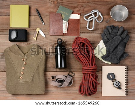 Overhead view of hiking gear laid out for a backpacking trip on a rustic wood floor. Items include, rope, gloves, sweater, carabiners  book, belt, cup, passport, wallet, canteen, compass, money, map,