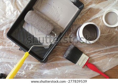 Overhead view of home painting equipment brush, roller, tray and paint pot