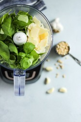 Overhead view of ingredients for fresh pesto in a food processor on a light grey kitchen countertop background