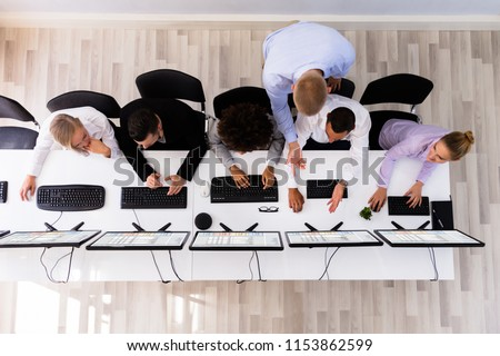 Overhead View Of Male Manager Discussing With Colleague Working On Computer #1153862599