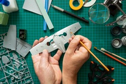 Overhead View Of Man Building Scale Model Aeroplane From Kit On Cutting BoardWith Tools And Materials