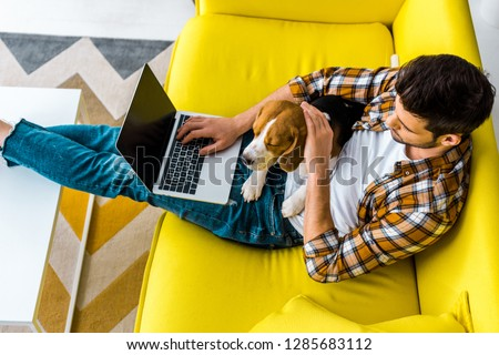 Photo of overhead view of man using laptop on sofa with cute dog