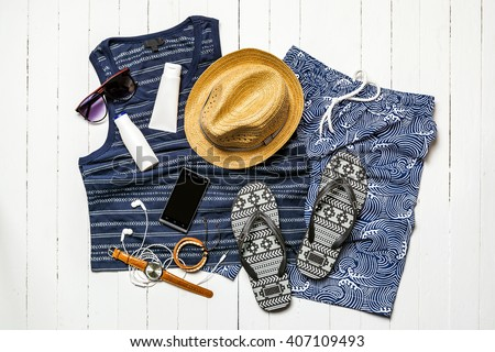 Overhead view of men\'s casual outfits of traveler, Summer holiday background, Beach accessories on white wood board, Vacation and travel items